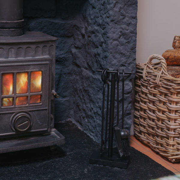 Black wood burning stove showing warm flames through the glass